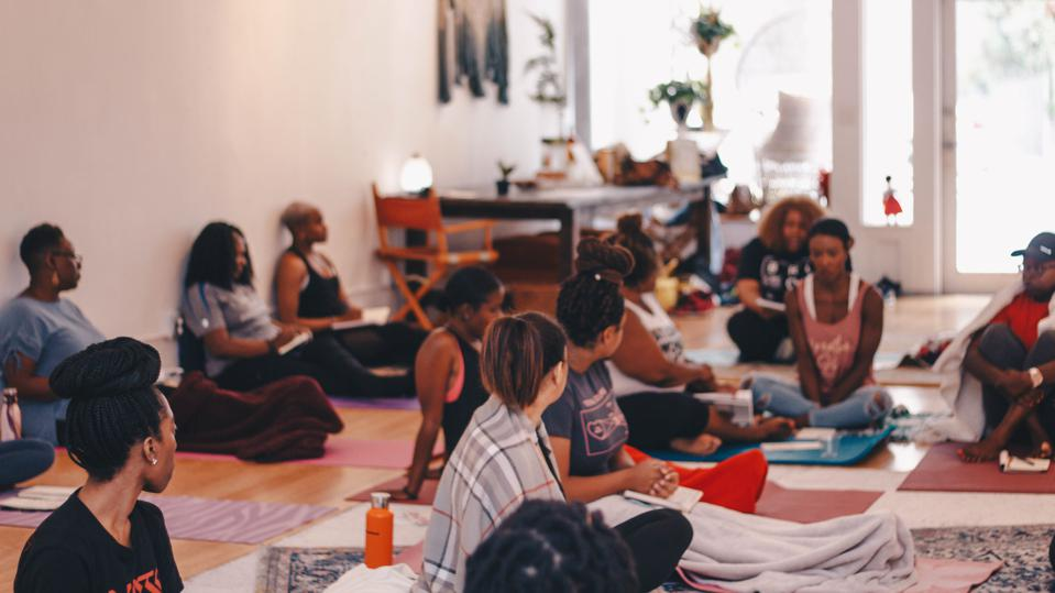 A group of women sit on the floor in a brightly lit breathwork class.