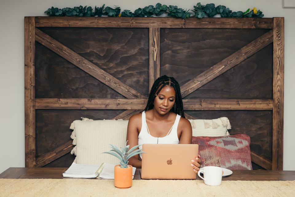 A black woman sits on a wooden bench at a wooden desk with a Mac laptop.