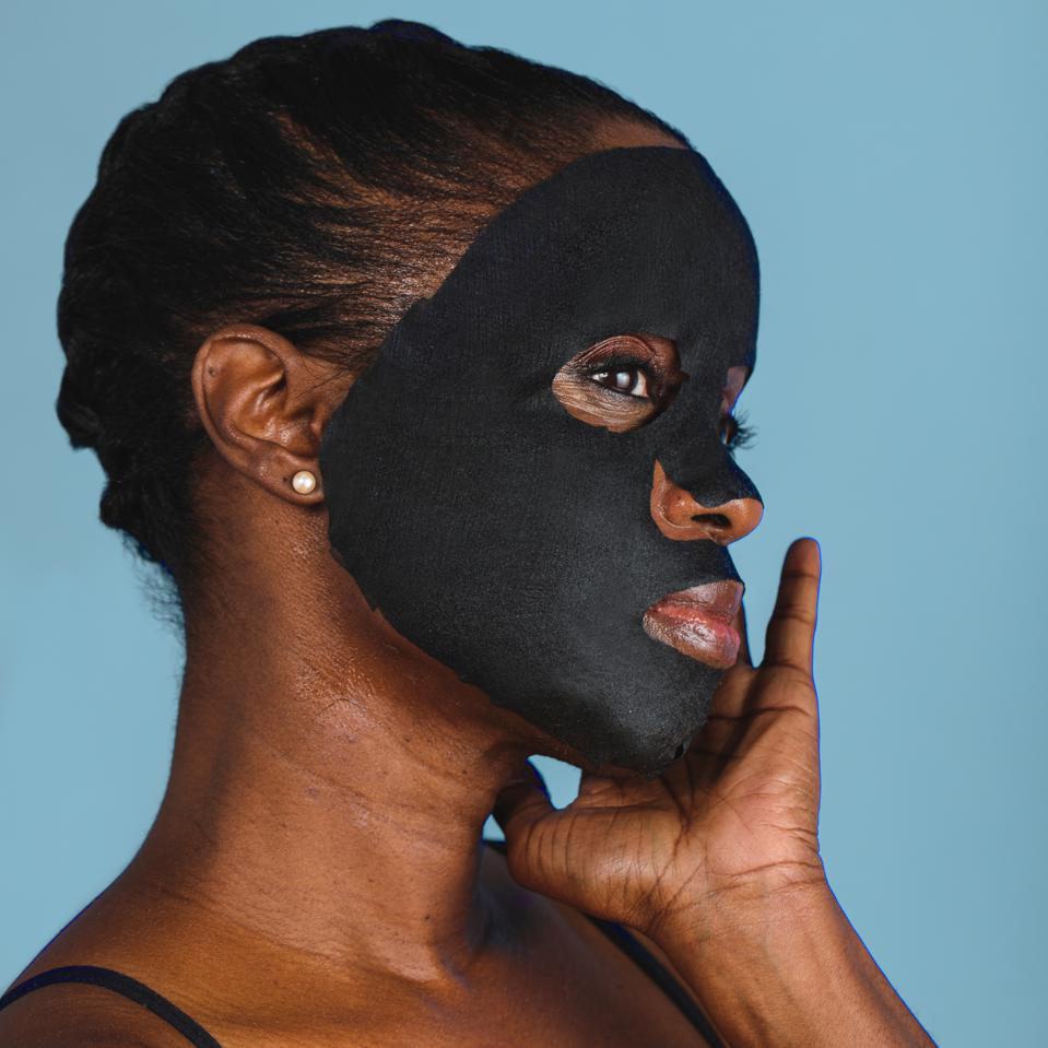 A black woman poses against a blue backdrop with a black face mask on.