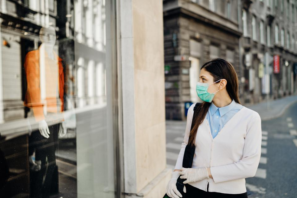 Woman with mask looking at a closed fashion clothes storefront.Clothing shopping during coronavirus outbreak shutdown.COVID-19 quarantine apparel retail store closures.Small business loss concept.