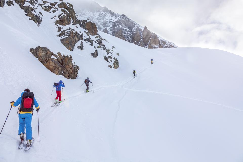 Group of people skiing in deep snow - ski tour, backcountry ski