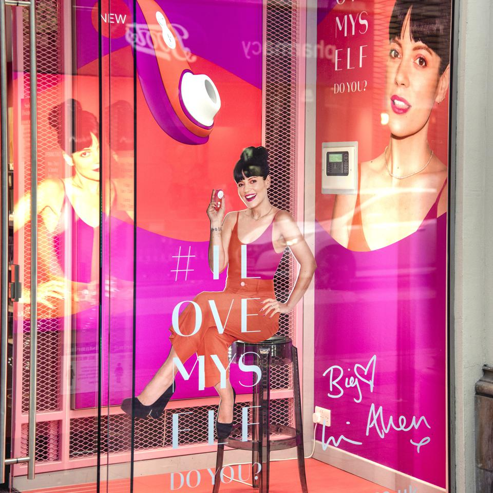 A Lily Allen mannequin holds a vibrator in a bright pink window display.