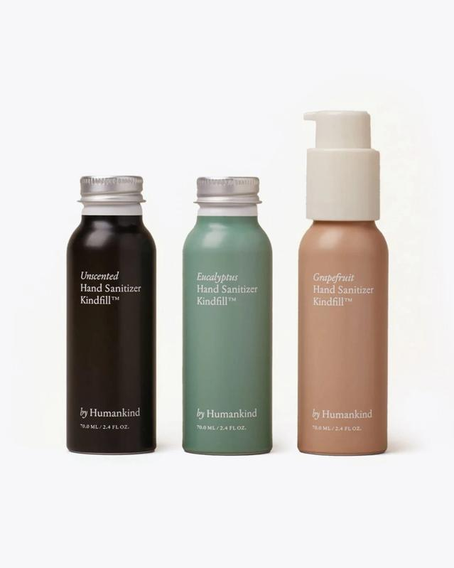 three pocket sized bottles of By Humankind's hand sanitizer in black, green, and peach packaging.