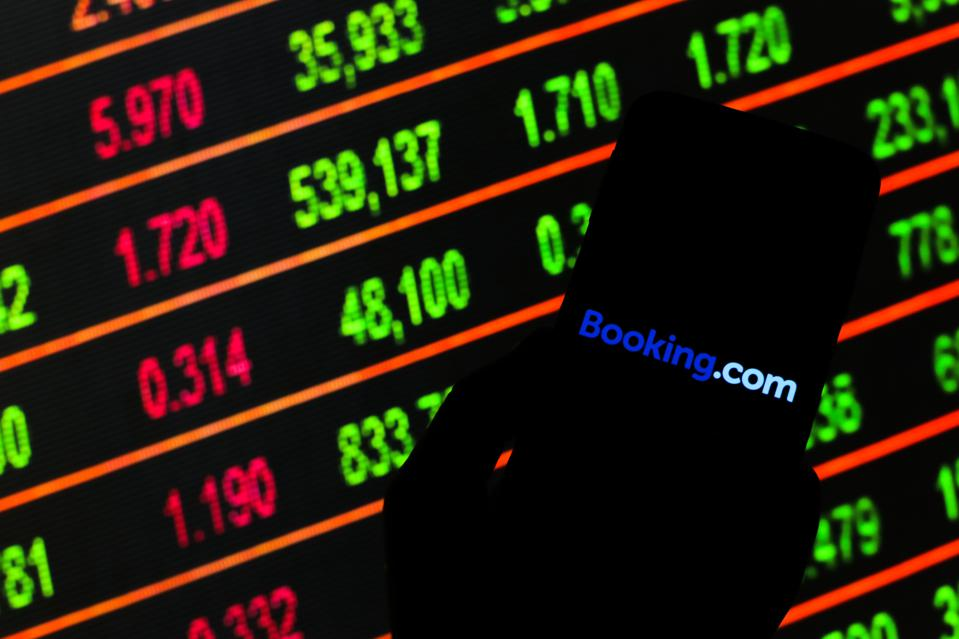 POLAND - 2020/03/13: In this photo illustration a Booking.com logo seen displayed on a smartphone. Stock market prices in the background as stock markets tumble all over the world. (Photo by Filip Radwanski/SOPA Images/LightRocket via Getty Images)