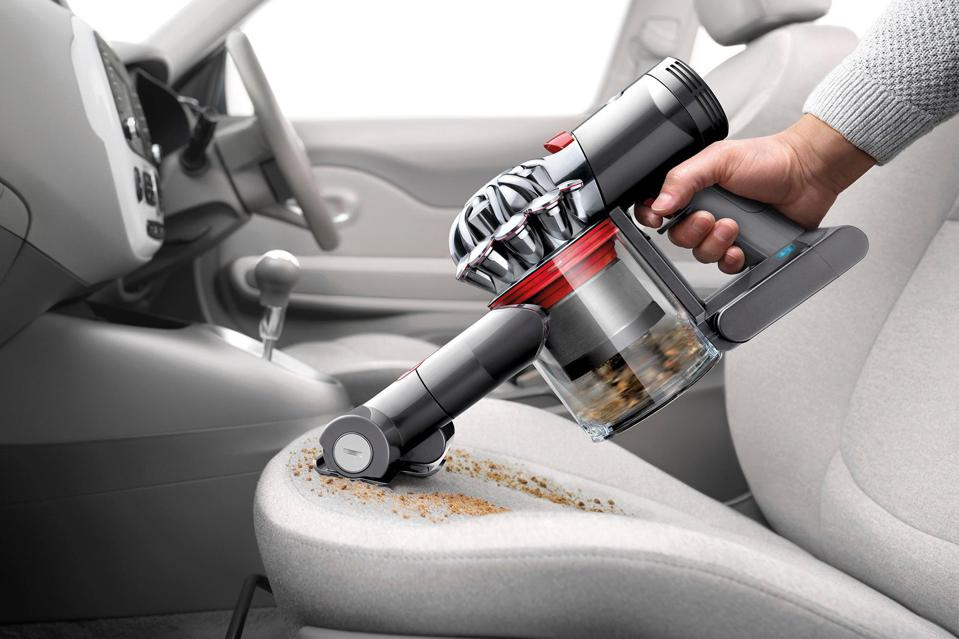 Close up shot of the Dyson V7 vacuum cleaning up a car seat