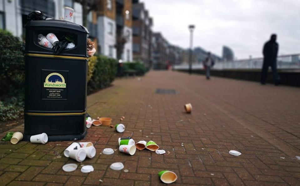 A trash can overflowing on London's riverside walkway.