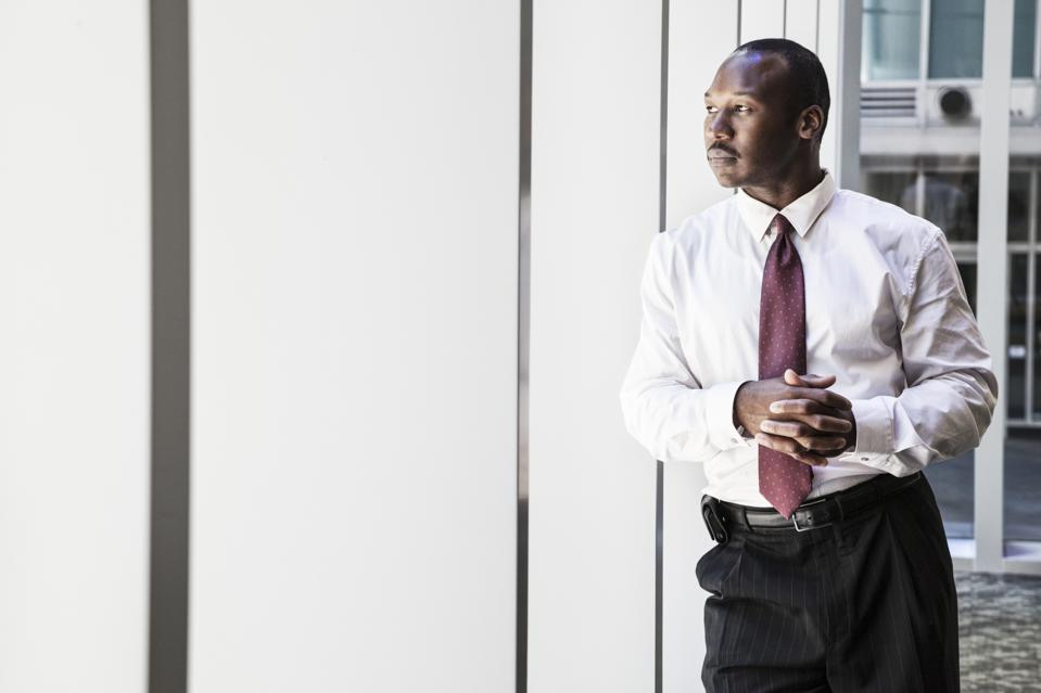 Black businessman in lobby of large business centre.