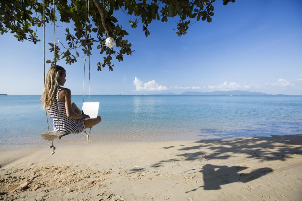 Thailand, woman using laptop on beach