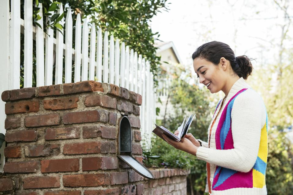 Side view of smiling woman reading mail at mailbox