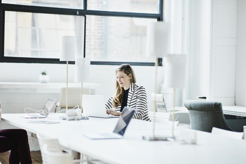 Businesswoman working on laptop in coworking office