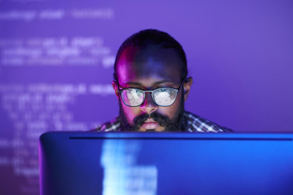 Programmer focused on monitor while programming. Programming language in background.