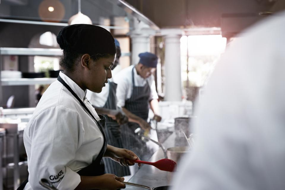 Chefs working on a row in the kitchen