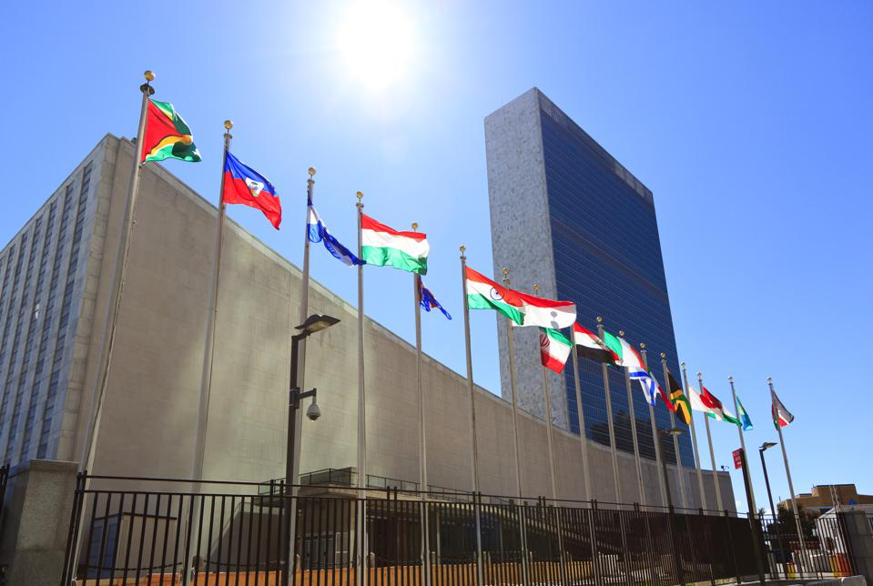 United Nations Headquarters with waving flags in New York, USA
