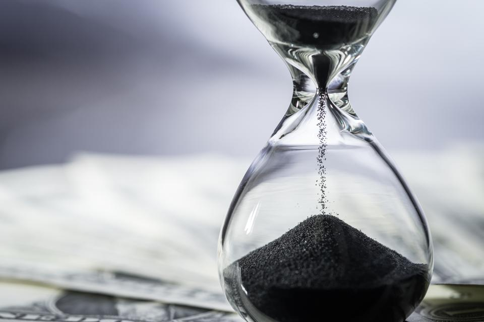 Closed up of sand falling in sandglass or hourglass on US Dollar bills as time running, long term investment or financial deadline concept
