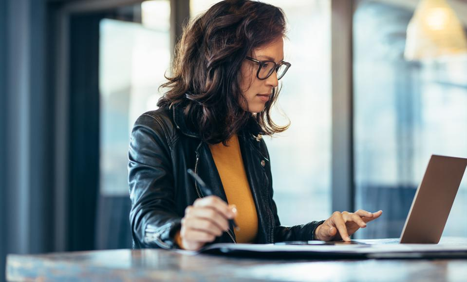 Businesswoman making notes looking at a laptop