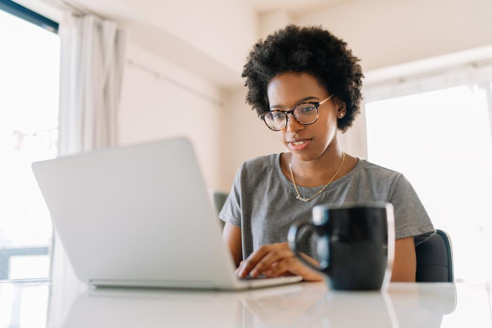 Young black beautiful woman using laptop at home