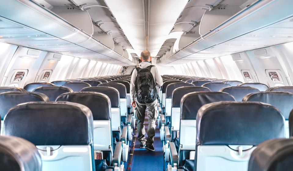 Inside view of commercial airplane with lonely man traveler