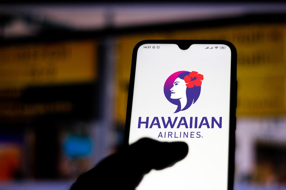 In this photo illustration the Hawaiian Airlines logo seen...