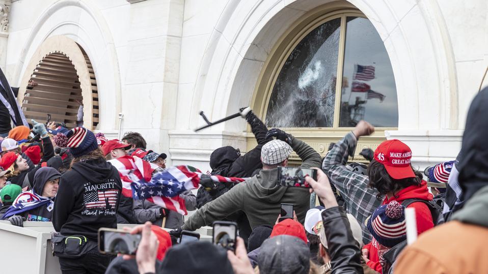 Pro-Trump protesters break windows of the Capitol building.