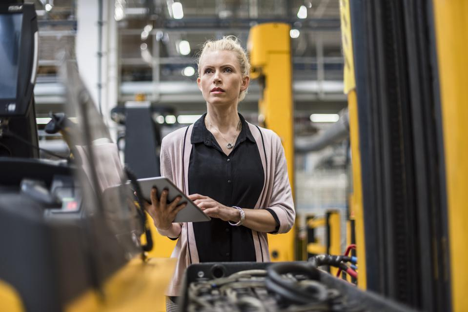 Woman holding tablet in factory shop floor