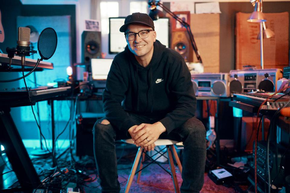 A white man with glasses and a black hoodie, sitting in a music studio.