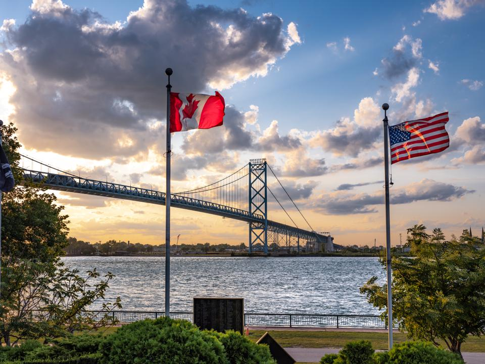 The Canadian and U.S. flags fly in front of the Detroit River and Ambassador Bridge.