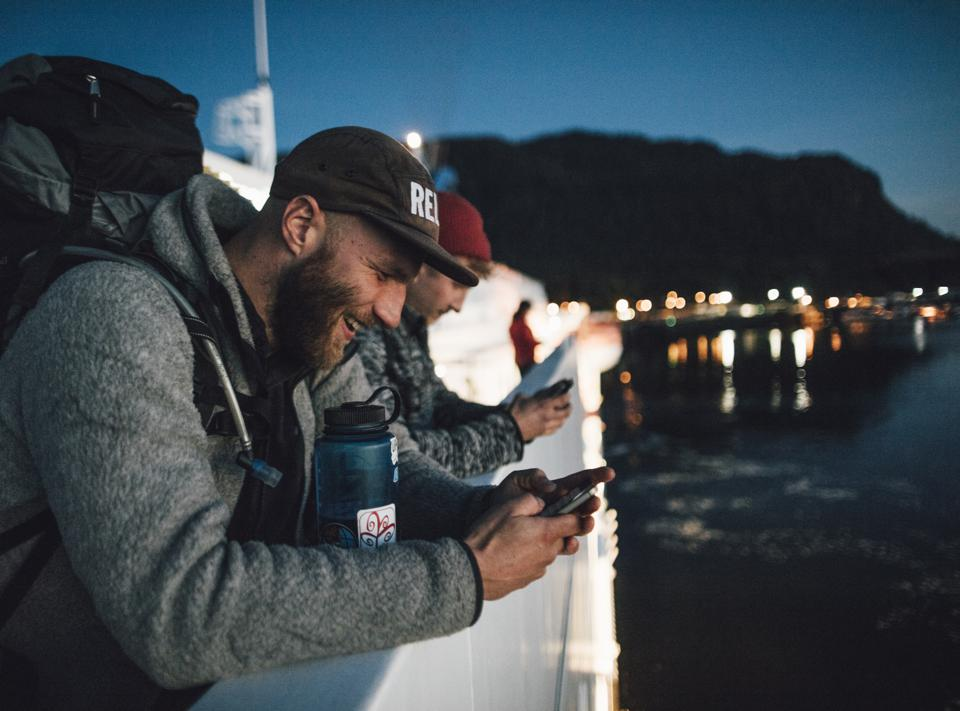 Canada, British Columbia, two men on a boat using cell phones at night