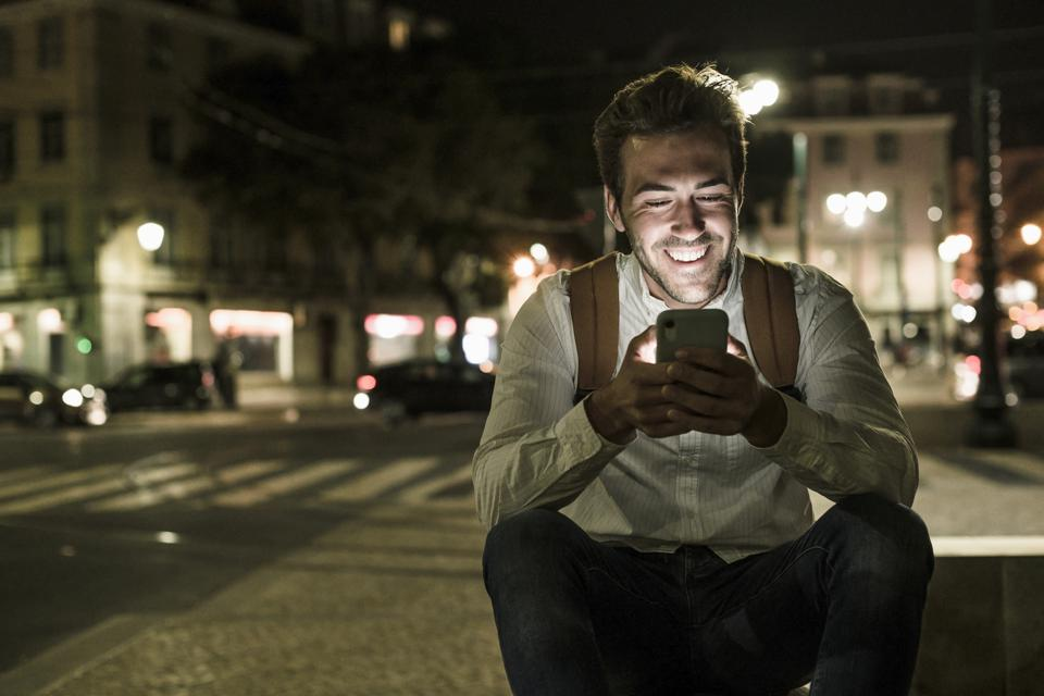 Portrait of happy young man using cell phone in the city by night, Lisbon, Portugal