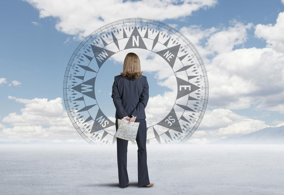 Businesswoman Looking At Compass On Horizon