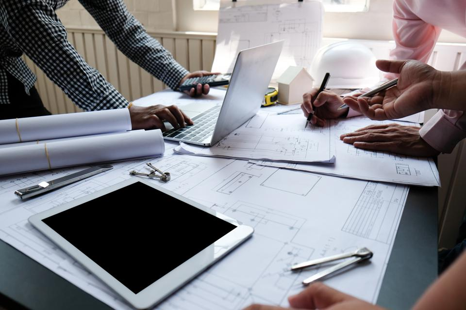 Midsection Of Architect Preparing Blueprints On Office Desk