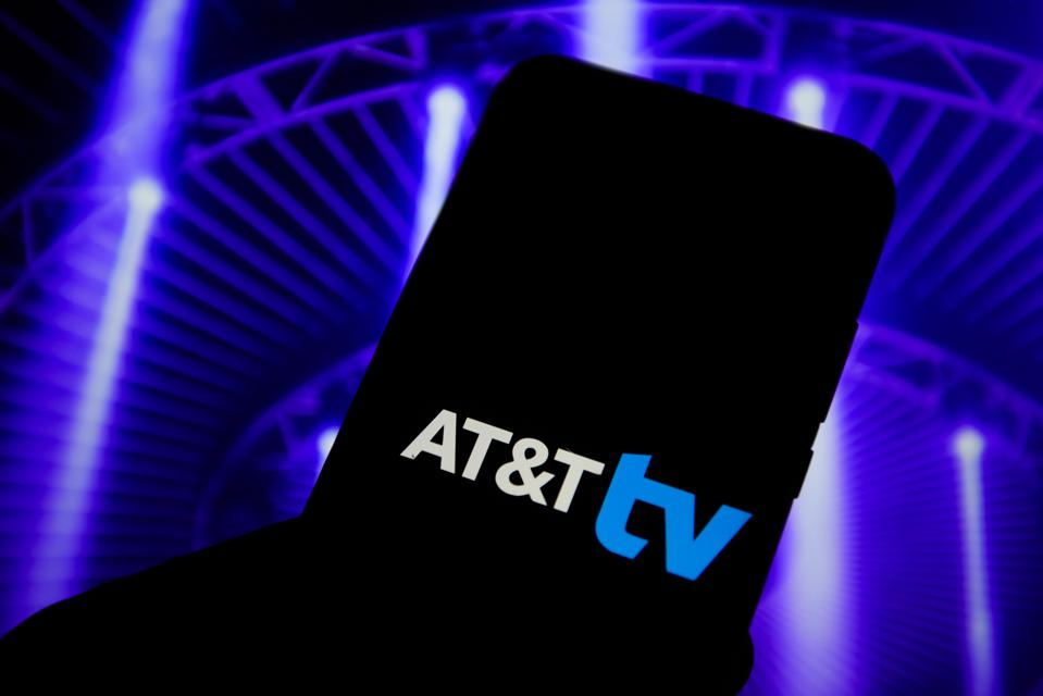 In this photo illustration an AT&T logo is seen displayed on...