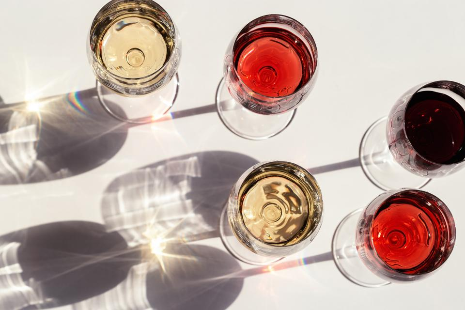 Red, rose and white wine top view in sunlight.  Dark shadows