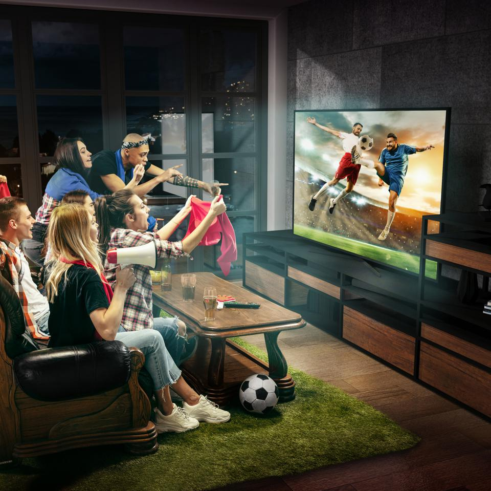 People loving watching sports on TV with their friends and family.