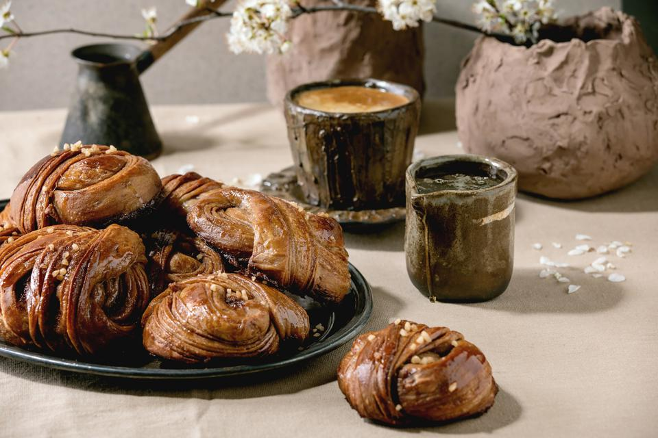 Kanelbulle traditional Swedish cinnamon sweet buns on vintage tray.  Cup of coffee.  jug of syrup.  branches of flowers on linen tablecloth.
