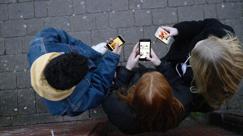 Group of friends on their mobile phones shot form above in the fading light