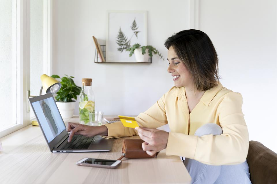 Happy beautiful young woman using laptop for online shopping at home