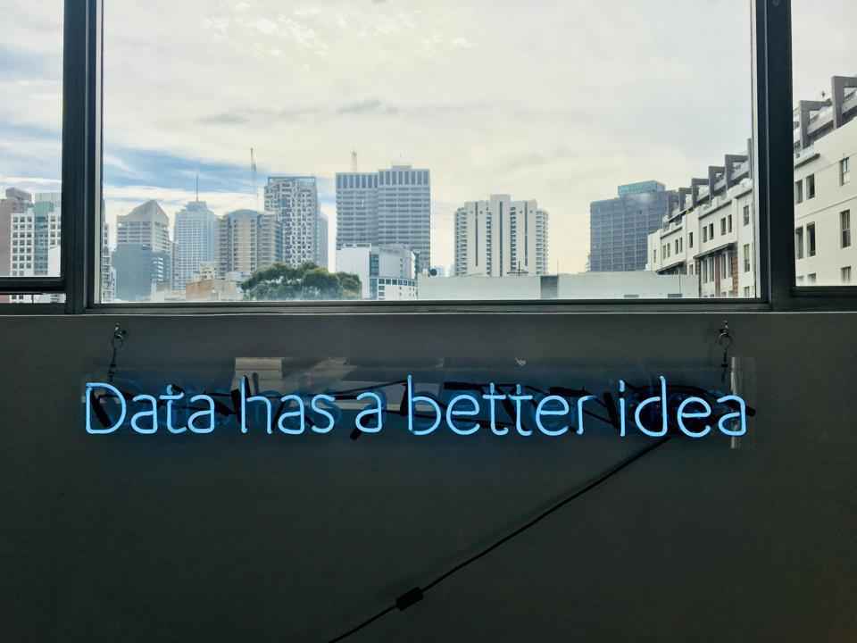 Neon sign positioned beneath an office window that reads: Data has a better idea.