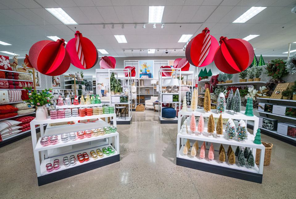 Target's home department with faux Christmas trees in various colors, wreaths and red and white pillows.