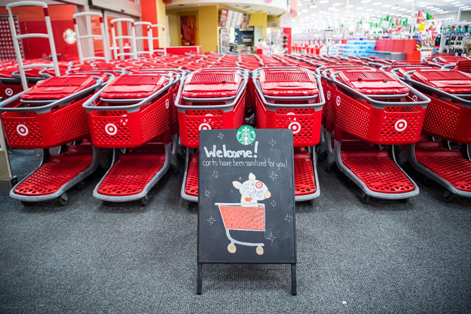 Red Target shopping carts lined up outside a store with a chalkboard sign featuring the retailer's mascot Bullseye in a wagon.