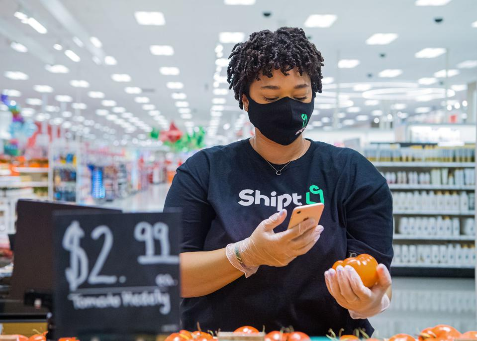 A Shipt employee choosing produce for an order.