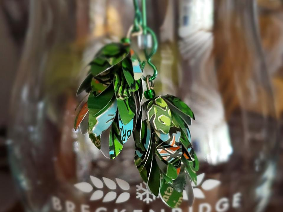 a pair of earrings made from scraps of beer cans