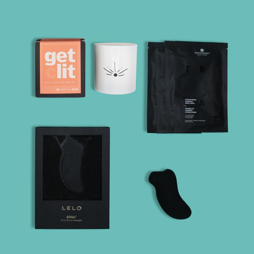 A flat lay of products including a white candle, face masks, and a black vibrator.