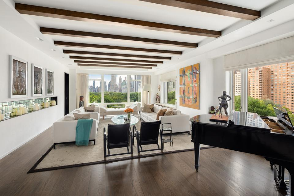 Spacious condominium living room with piano, art