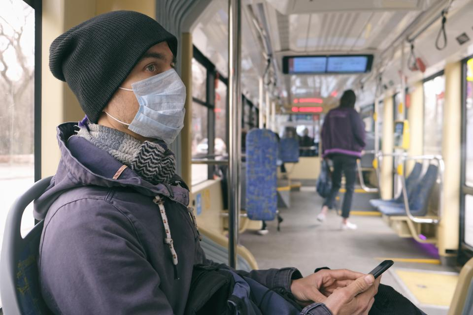 Adult man with medical protective mask and gloves inside public transport tram using smartphone. Disease outbreak, coronavirus covid-19 pandemic, virus protection, air pollution.