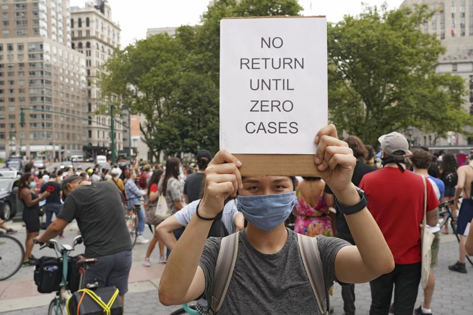 A protester holds a placard that says No return until zero...