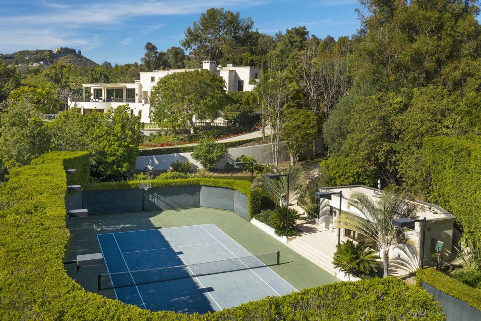 A tennis court ensconced by manicured landscaping with Wynn's home in background.