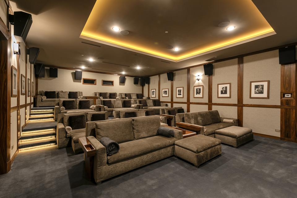 The roomy theater with tiered levels of comfortable couches.