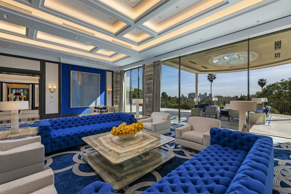 The living room, featuring blue velvet couches and carpeting, opens up onto the terrace, with another lounge area, and views of the city.