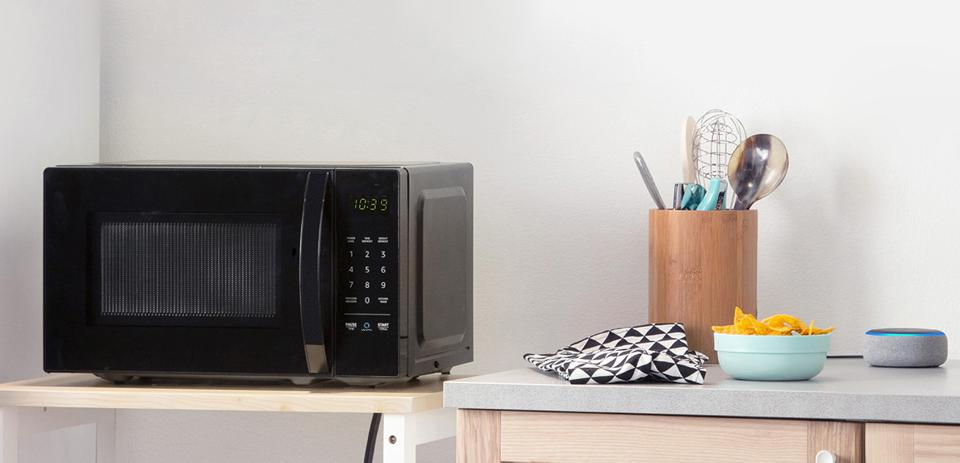 The AmazonBasics microwave sits on a countertop with an Echo Dot close by