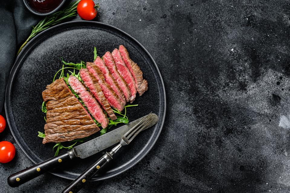 Grilled and cut Flat Iron steak. Marble beef meat. Black background. Top view. Copy space